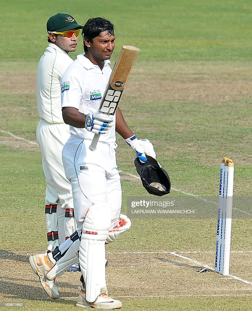 Sri Lanka's cricketer Kumar Sangakkara (R) raises his bat in celebration after scoring a century (100 runs) as Bangladeshi wicketkeeper and captain Mushfiqur Rahim look on during the second day of their second Test match between Sri Lanka and Bangladesh at the R. Premadasa Cricket Stadium in Colombo on March 17, 2013.
