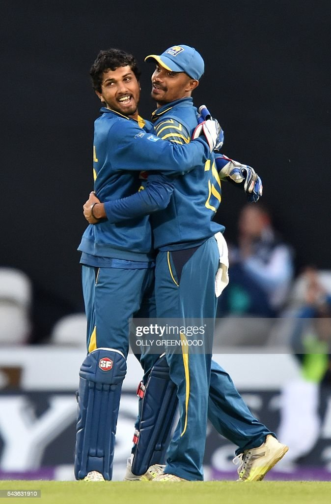 Sri Lanka's Danushka Gunathilaka (R) celebrates with Sri Lanka's Dinesh Chandimal after catching England's captain Eoin Morgan (not pictured) during play in the fourth One Day International (ODI) cricket match between England and Sri Lanka at The Oval cricket ground in London on June 29, 2016. England's victory target was revised to 308 off 42 overs due to the weather having seen the tourists show real guile and style in their innings. / AFP / OLLY