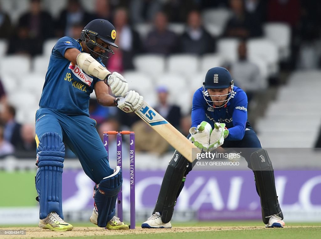 Sri Lanka's Danushka Gunathilaka (L) plays a shot watched by England's Jonny Bairstow (R) during play in the fourth One Day International (ODI) cricket match between England and Sri Lanka at The Oval cricket ground in London on June 29, 2016. England captain Eoin Morgan elected to field after winning the toss in the fourth one-day international against Sri Lanka at The Oval on Wednesday. With light rain around and dark grey skies, Morgan clearly felt his bowlers could utilise the favourable bowling conditions with further down pours forecast during the afternoon and evening. ECB