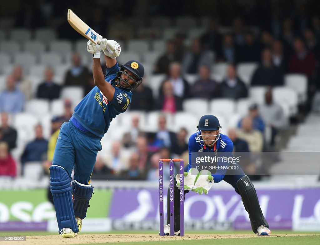 Sri Lanka's Danushka Gunathilaka (L) plays a shot watched by England's Jos Buttler (R) during play in the fourth One Day International (ODI) cricket match between England and Sri Lanka at The Oval cricket ground in London on June 29, 2016. England captain Eoin Morgan elected to field after winning the toss in the fourth one-day international against Sri Lanka at The Oval on Wednesday. With light rain around and dark grey skies, Morgan clearly felt his bowlers could utilise the favourable bowling conditions with further down pours forecast during the afternoon and evening. ECB