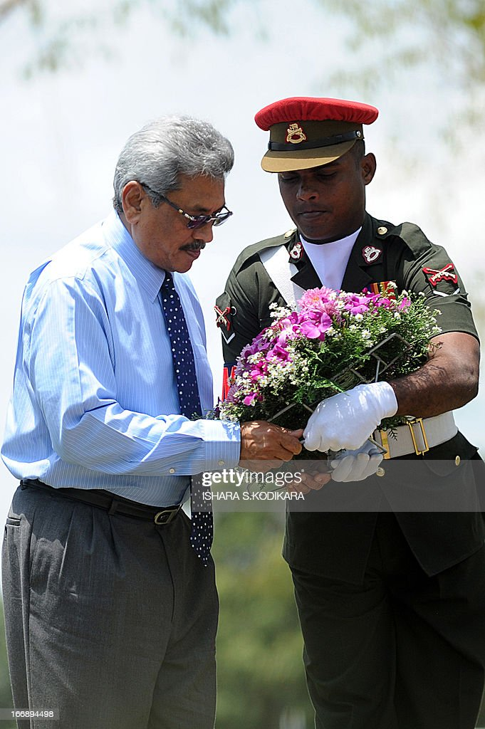 Sri Lanka's Defence secretary Gotabhaya Rajapakse (L) places flowers at a monument during a ceremony in the eastern region of Thoppigala on April 18, 2013. The monument commemorated government troops killed while wresting control over the region from Tamil Tiger rebels during the war. AFP PHOTO/ Ishara S. KODIKARA