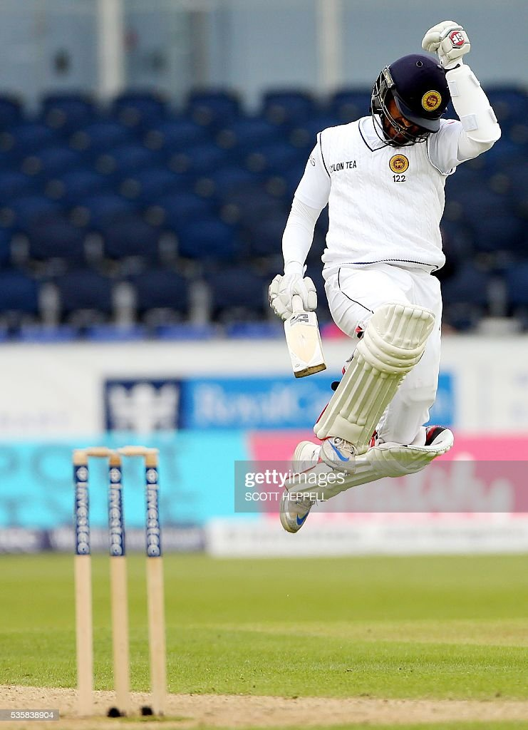 Sri Lanka's Dinesh Chandimal celebrates after scoring 100 runs on the fourth day of the second test cricket match between England and Sri Lanka at the Riverside in Chester-le-Street, north east England, on May 30, 2016. / AFP / SCOTT