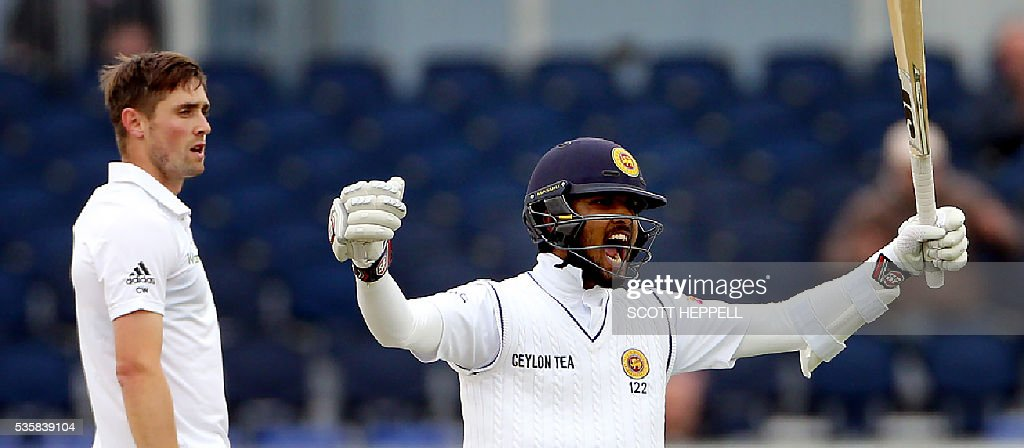 Sri Lanka's Dinesh Chandimal (R) celebrates after scoring 100 runs on the fourth day of the second test cricket match between England and Sri Lanka at the Riverside in Chester-le-Street, north east England, on May 30, 2016. / AFP / SCOTT