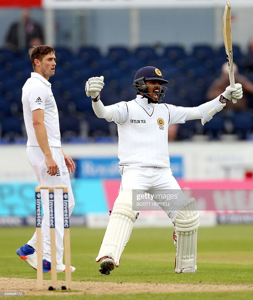 Sri Lanka's Dinesh Chandimal (R) celebrates scoring 100 runs on the fourth day of the second test cricket match between England and Sri Lanka at the Riverside in Chester-le-Street, north east England, on May 30, 2016. / AFP / SCOTT