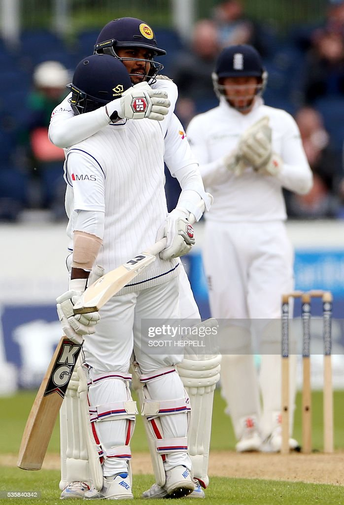 Sri Lanka's Dinesh Chandimal (2nd L) embraces team-mate Rangana Herath (L) after Herath scored his 50 runs on the fourth day of the second test cricket match between England and Sri Lanka at the Riverside in Chester-le-Street, north east England, on May 30, 2016. / AFP / SCOTT