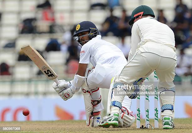 Sri Lanka's Dinesh Chandimal plays a shot past Australia's wicketkeeper Peter Nevill during the first day of the opening Test cricket match between...