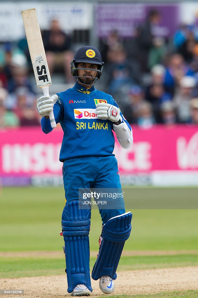 Sri Lanka's Dinesh Chandimal raises his bat as he reaches his 50 during play in the third one day international (ODI) cricket match between England and Sri Lanka at Bristol cricket ground in Bristol, south-west England, on June 26, 2016. England captain Eoin Morgan won the toss and elected to field against Sri Lanka in the third one-day international at Bristol on Sunday. / AFP / JON