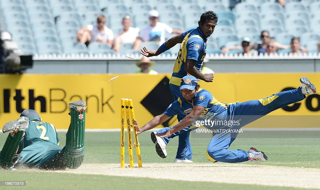 Sri Lanka's fastbowler Angelo Mathews (C) looks on as teammate Jeevan Mendis (R) dives to unsuccussfully run-out Australia's captain George Bailey (L) during the first one-day international between Australia and Sri Lanka at the Melbourne Cricket Ground on January 11, 2013.
