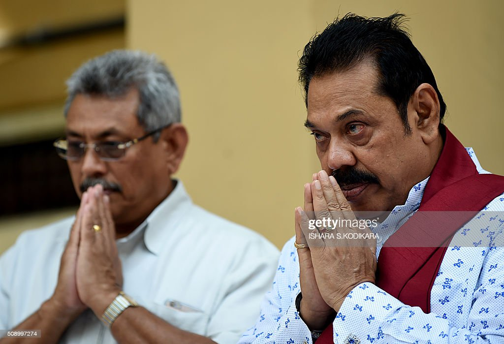 Sri Lankas former president Mahinda Rajapakse (R) and his brother Gotabhaya Rajapakse (L), who was the country's defence secretary in 2009, pray in Colombo on February 8, 2016 as they join a petition against a UN-mandated investigation into alleged war crimes during the final stages of the islands Tamil separatist war. Former president Mahinda Rajapakse and his brother on February 8 denounced a visit by UN human rights chief Zeid Ra'ad Al Hussein to Sri Lanka as a 'big joke' and renewed their opposition to a UN-mandated war crimes probe. AFP PHOTO/ Ishara S. KODIKARA / AFP / Ishara S.KODIKARA