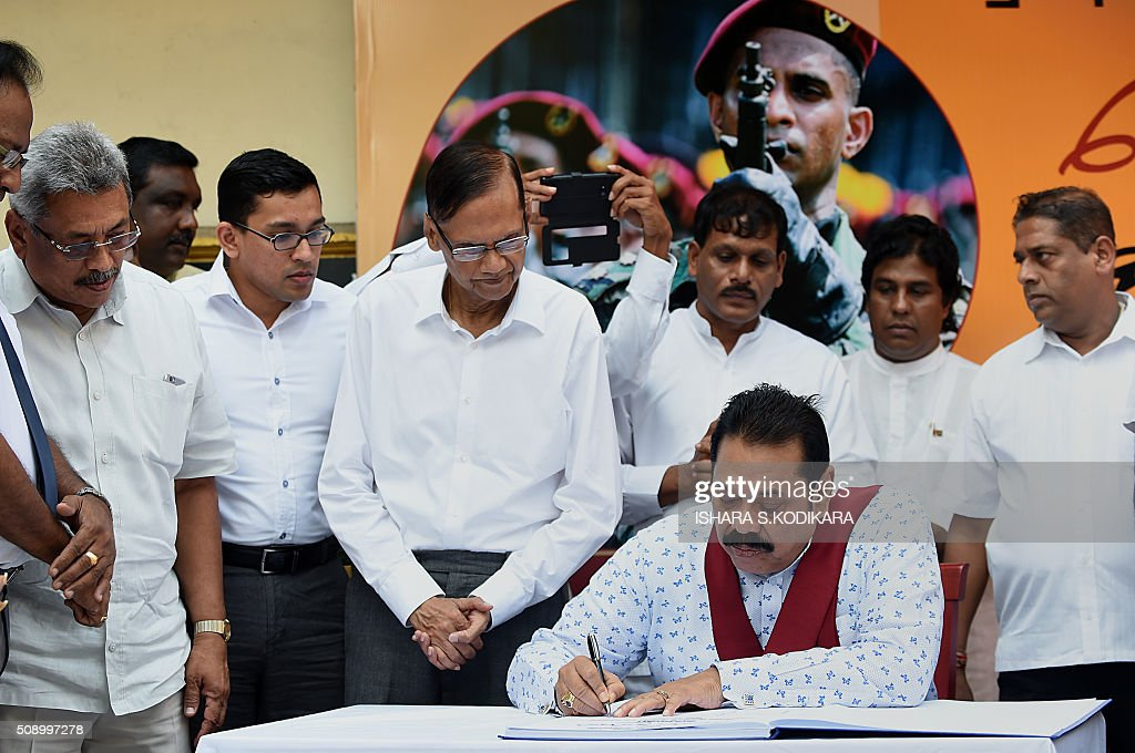 Sri Lankas former president Mahinda Rajapakse (bottom R) signs a petition in Colombo on February 8, 2016 against a UN-mandated investigation into alleged war crimes during the final stages of the islands Tamil separatist war. Former president Mahinda Rajapakse and his brother on February 8 denounced a visit by UN human rights chief Zeid Ra'ad Al Hussein to Sri Lanka as a 'big joke' and renewed their opposition to a UN-mandated war crimes probe. AFP PHOTO/ Ishara S. KODIKARA / AFP / Ishara S.KODIKARA