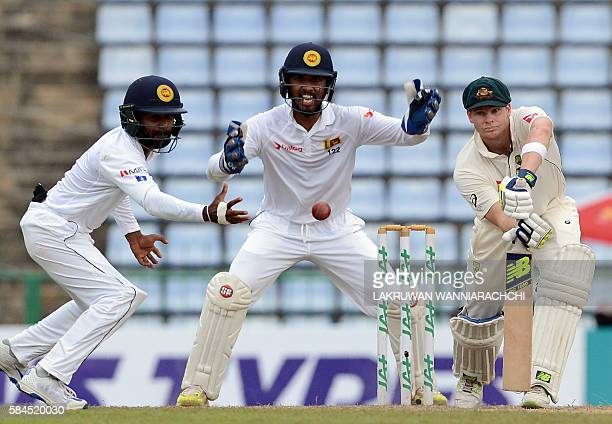 TOPSHOT Sri Lanka's Kaushal Silva attempts to field a ball hit by Australia's captain Steven Smith as wicketkeeper Dinesh Chandimal looks on during...