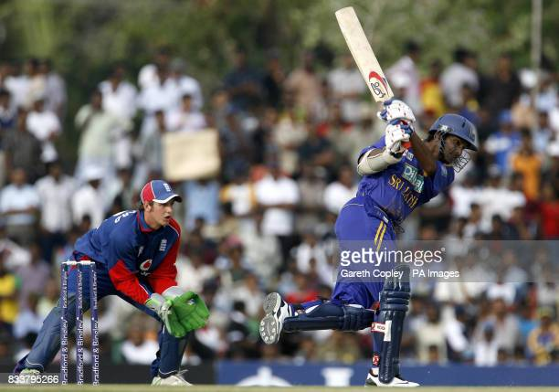 Sri Lanka's Kumar Sangakkara hits down the pitch watched by England keeper Phil Mustard during the First One Day International at Rangiri Dambulla...