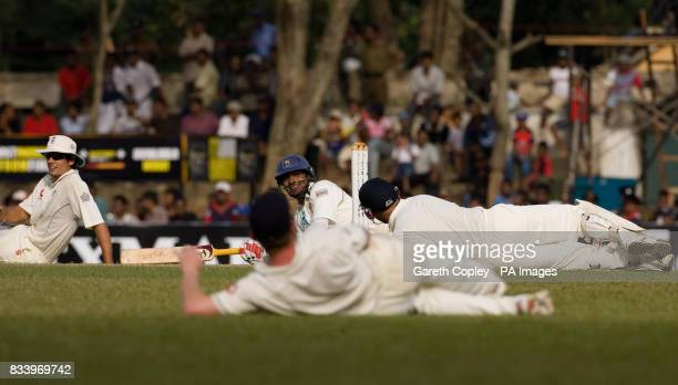 Sri Lanka's Kumar Sangakkara lies on the ground with the England fielders as a swarm of bees stops play during the first Test match at Asgiriya...