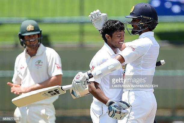 Sri Lanka's Kusal Mendis is congratulated by teammate Dinesh Chandimal after scoring a century during the third day of the opening Test match between...