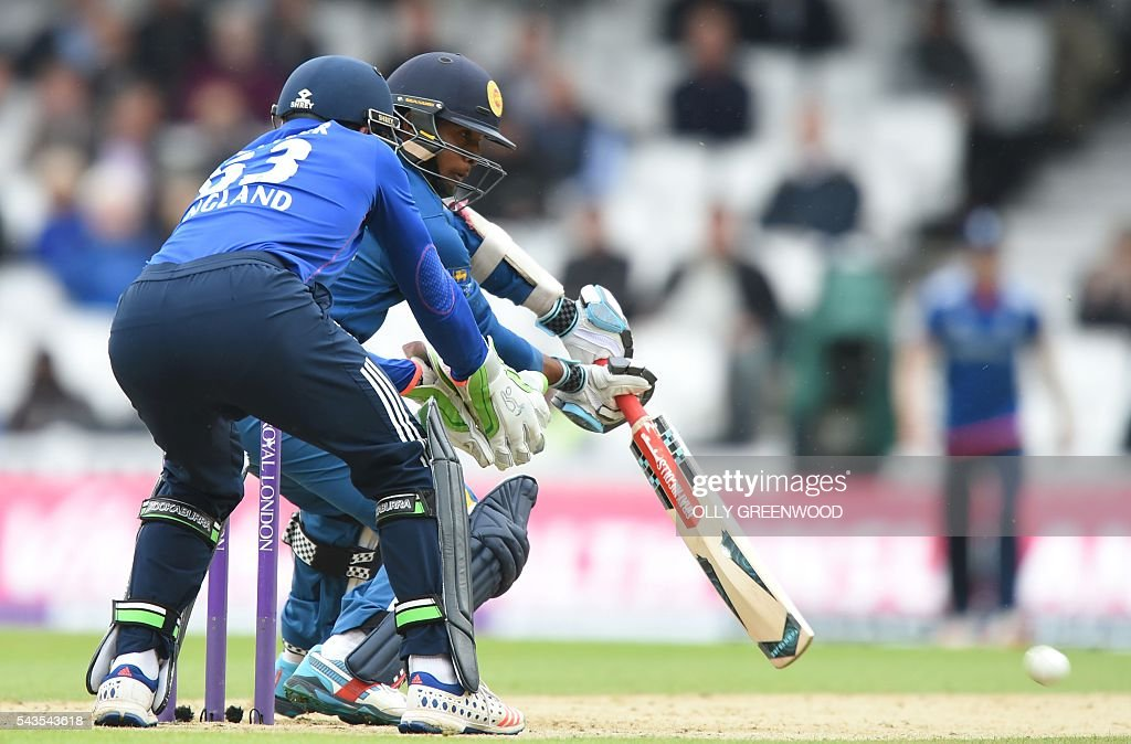 Sri Lanka's Kusal Mendis (R) plays a shot watched by England's Jos Buttler (L) during play in the fourth One Day International (ODI) cricket match between England and Sri Lanka at The Oval cricket ground in London on June 29, 2016. England captain Eoin Morgan elected to field after winning the toss in the fourth one-day international against Sri Lanka at The Oval on Wednesday. With light rain around and dark grey skies, Morgan clearly felt his bowlers could utilise the favourable bowling conditions with further down pours forecast during the afternoon and evening. ECB