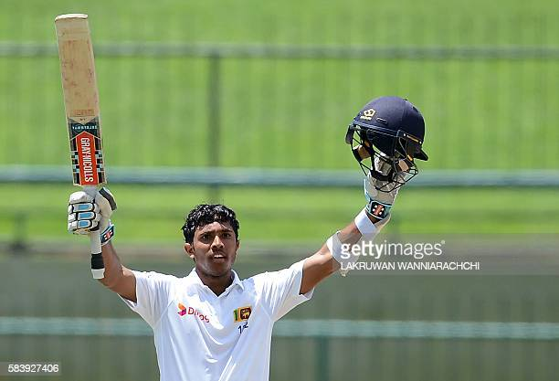 Sri Lanka's Kusal Mendis raises his bat and helmet in celebration after scoring a century during the third day of the opening Test match between Sri...