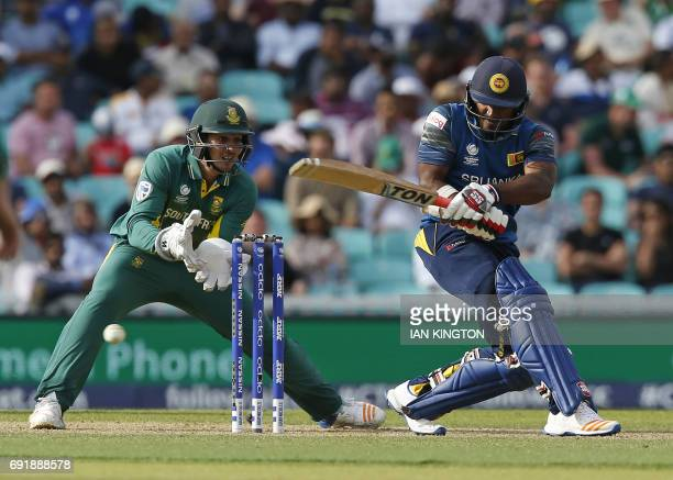 Sri Lankas Kusal Perera plays a shot as South Africas Quinton de Kock looks on during the ICC Champions Trophy match between South Africa and Sri...