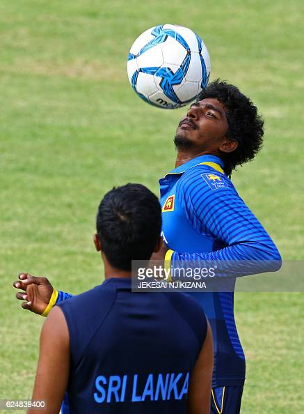 Sri Lanka's Lakshan Sandakan plays with a football after play was called off following rainfall during the fourth ODI match between Zimbabwe and Sri...