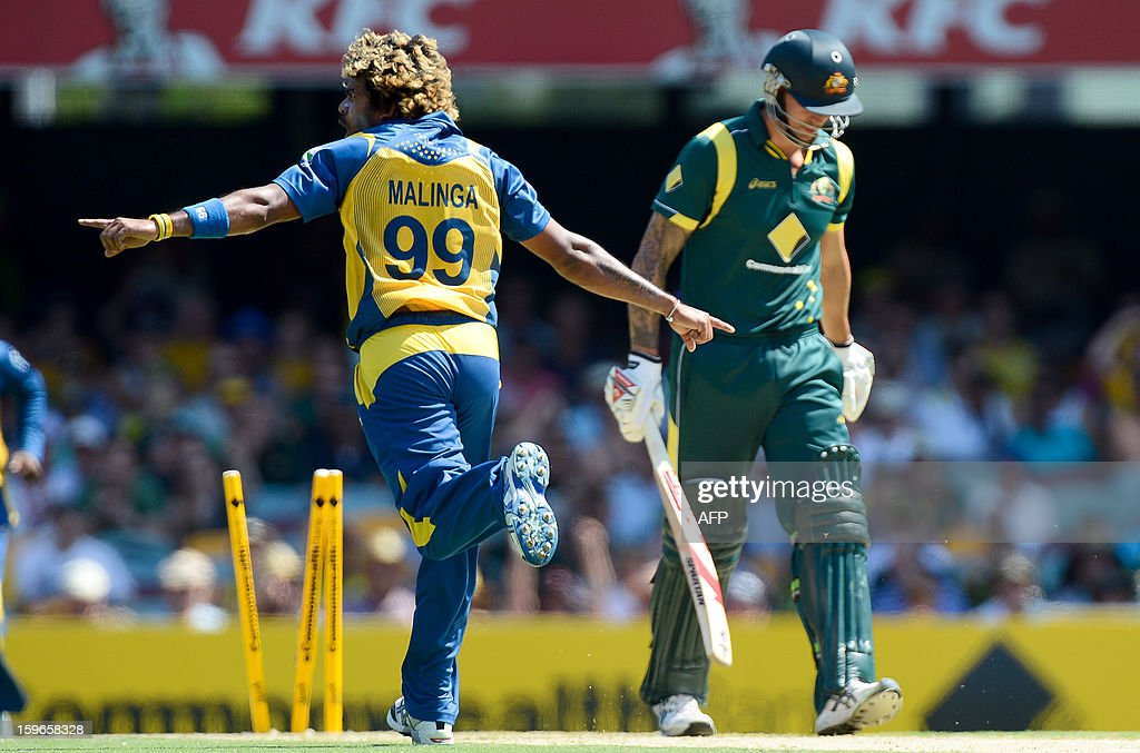 Sri Lanka's Lasith Malinga (L) celebrates after clean bowling Australia's batsman Mitchell Johnson (R) during their one-day international cricket match at the Gabba in Brisbane on January 18, 2013.  AFP PHOTO / Bradley KANARIS USE