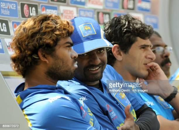 Sri Lanka's Lasith Malinga chats with team mate Muttiah Muralitharan on the bench