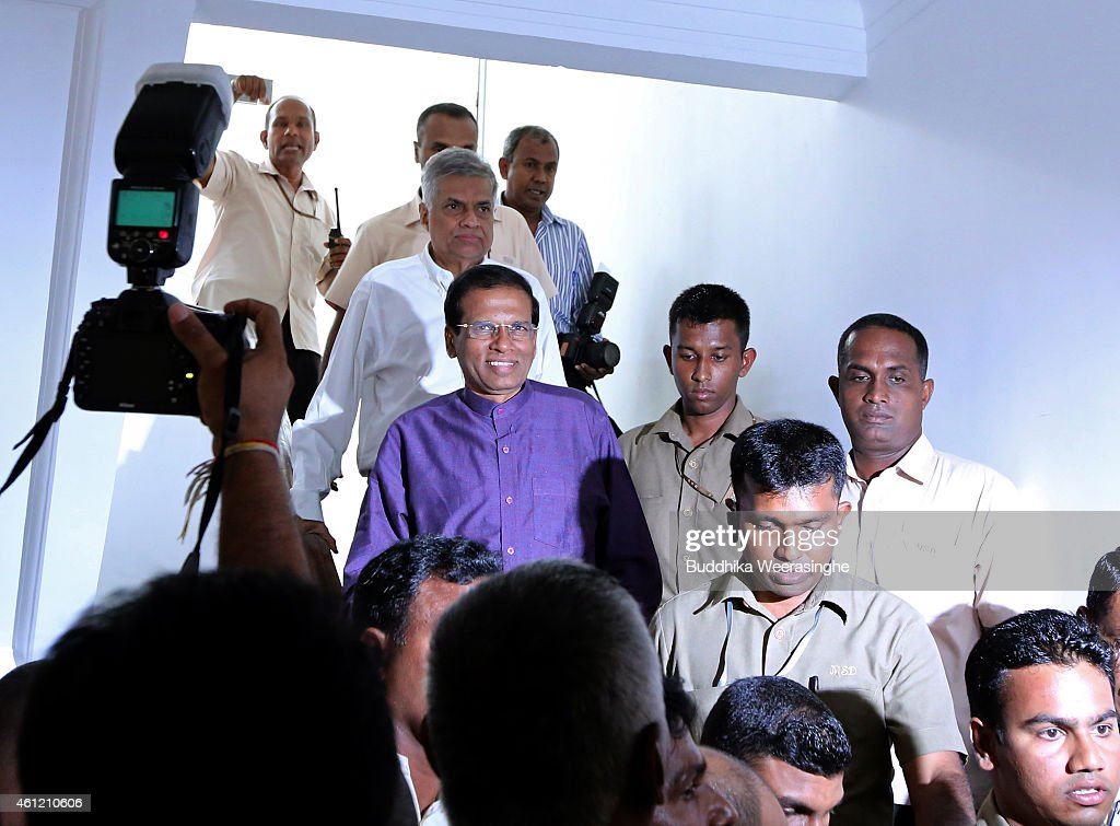 Sri Lanka's newly elected president Maithripala Sirisena (in purple) is seen with opposition leader Ranil Wickremesinghe (above him) as they leave the opposition leader's office on January 9, 2015 in Colombo, Sri Lanka. Maithripala Sirisena is to be sworn in this evening as the new President of the Democratic Socialist Republic of Sri Lanka.