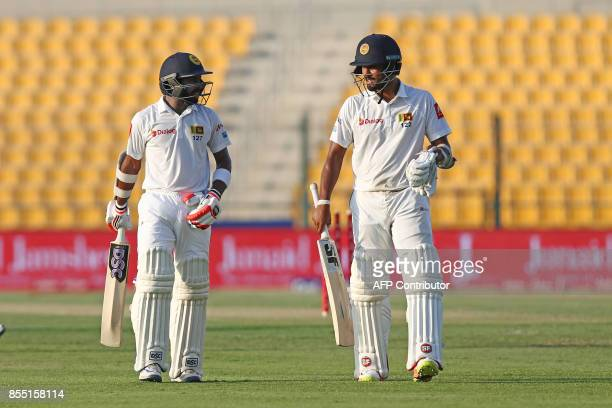 Sri Lanka's Niroshan Dickwella and captain Dinesh Chandimal walking on the first day of the first Test cricket match between Pakistan and Sri Lanka...