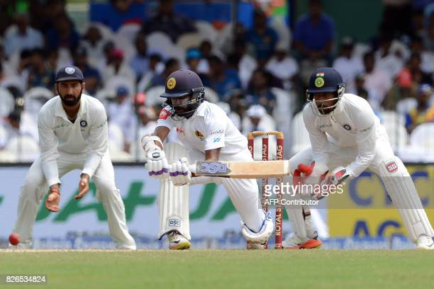 Sri Lanka's Niroshan Dickwella is watched by India's wicketkeeper Wriddhiman Saha as he plays a shot during the third day of the second Test cricket...
