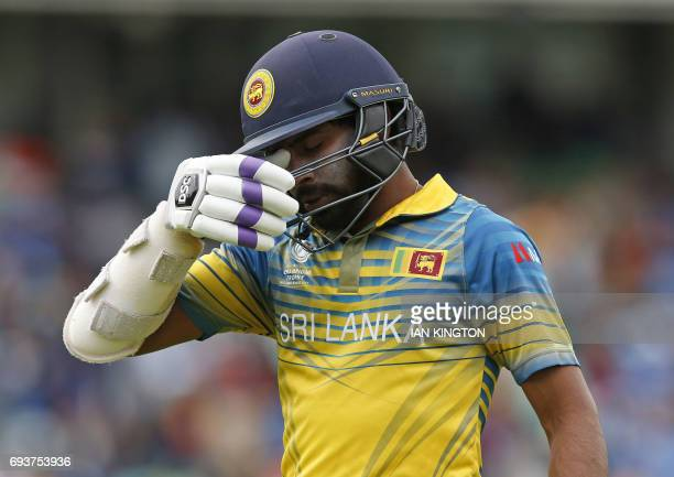 Sri Lankas Niroshan Dickwella reacts as he walks back to the pavilion after getting out for 7 runs during the ICC Champions Trophy match between...