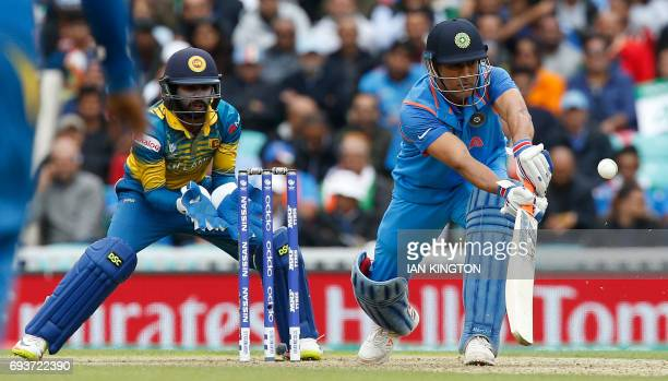 Sri Lanka's Niroshan Dickwella watches as India's MS Dhoni plays a shot during the ICC Champions Trophy match between India and Sri Lanka at The Oval...