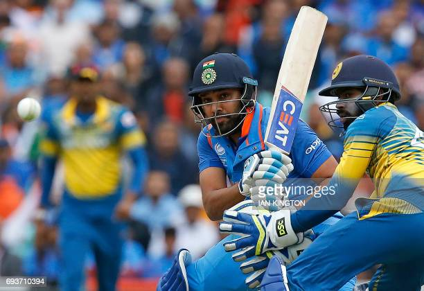 Sri Lanka's Niroshan Dickwella watches as India's Rohit Sharma plays a shot for four runs during the ICC Champions Trophy match between India and Sri...