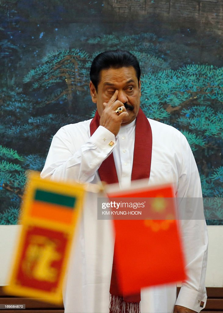 Sri Lanka's President Mahinda Rajapaksa rubs his eye as he attends a signing ceremony with China's President Xi Jinping (not pictured) at the Great Hall of the People in Beijing on May 28, 2013.