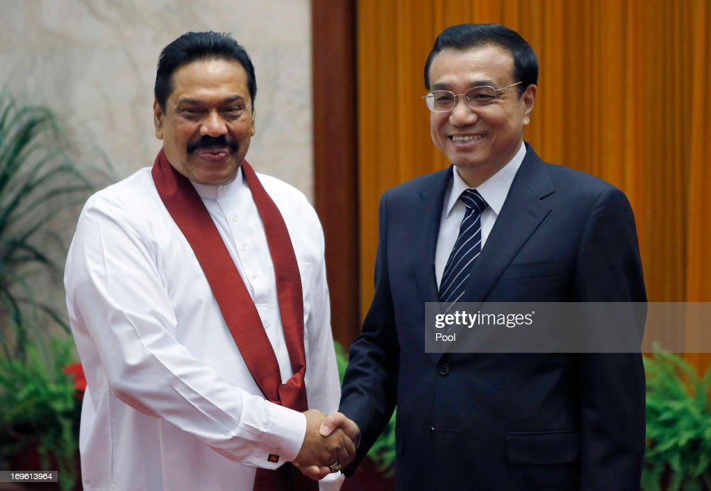 Sri Lanka's President Mahinda Rajapaksa (L) shakes hands with China's Premier Li Keqiang (R ) at the Great Hall of the People on May 29, 2013 in Beijing, China.