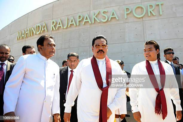 Sri Lanka's president Mahinda Rajapakse flanked by his eldest son and parliamentarian Namal Rajapakse and Prime Minister D M Jayaratne walks past the...