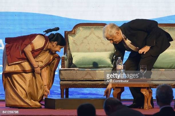 Sri Lankas Prime Minister Ranil Wickremesinghe and Indias Foreign Minister Sushma Swaraj position her foot stool at the opening of a twoday Indian...