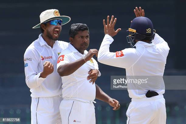 Sri Lanka's Rangana Herath and capatain Dinesh Chandimal celebrate taking the wicket of Zimbabwe's Hamilton Masakadza during the third day's play of...