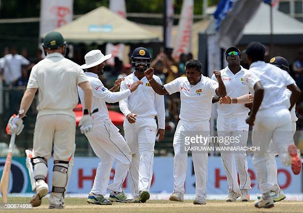 Sri Lanka's Rangana Herath celebrates with teammates after he dismissed Australia's Adam Voges during the final day of the third and final Test...