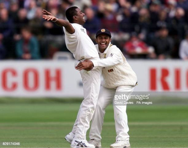 Sri Lanka's Ruchira Perera is embraced by teammate Hashan Tillakaratne after trapping England batsman Graham Thorpe lbw for 27 during the third day...