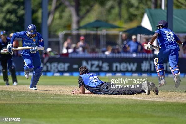 Sri Lanka's Tillakaratne Dilshan and teammate Lahiru Thirimanne run as New Zealand's Kyle Mills falls after trying to take a catch during the sixth...