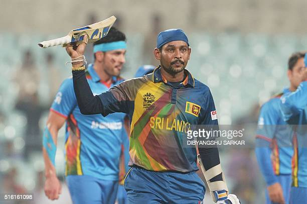Sri Lanka's Tillakaratne Dilshan raise the bat to celebrate the team's win after the World T20 cricket tournament match between Afghanistan and Sri...