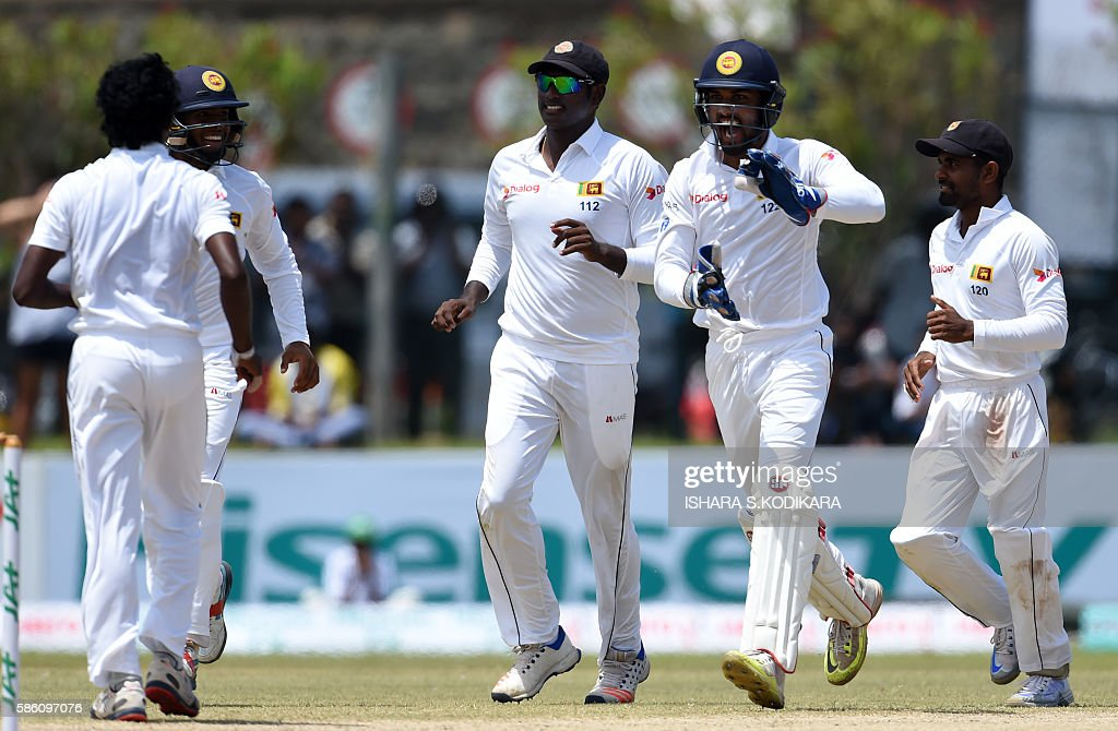 Sri Lanka's wicketkeeper Dinesh Chandimal celebrates with teammate Lakshan Sandakan after he dismissed unseen Australian batsman Mitchell Marsh...