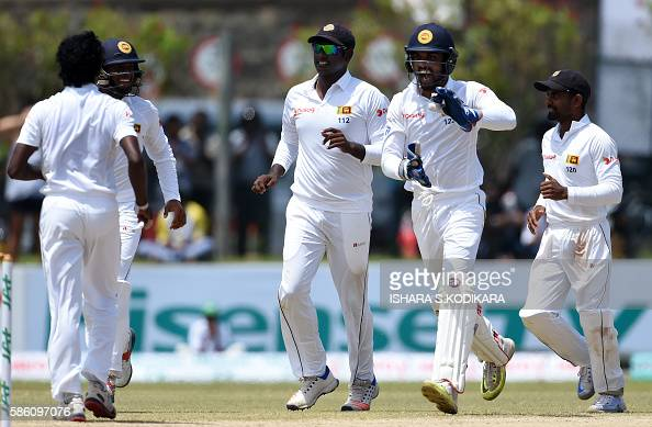 Sri Lanka's wicketkeeper Dinesh Chandimal celebrates with teammate Lakshan Sandakan after he dismissed unseen Australian batsman Mitchell Marsh...