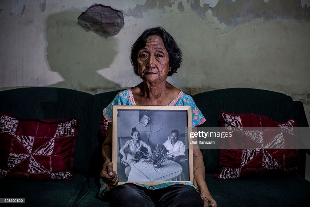 Sri Muhayati, 75 years old, holds a photograph of her parents at his house on May 06, 2016 in Yogyakarta, Indonesia. Sri, was a student, who spent 5 years imprisoned without trial for suspected ties to the Indonesian Communist Party (PKI). She was imprisoned because her father Muhadi, suspected ties to the Indonesian Communist Party (PKI) and was die executed. To search for evidence of massacre grave in 2000, she and other survivors, digging the massacre graves in Wonosobo, Central Java, and found bones that she believed her father. Survivors of Indonesia's anti-communist massacres in 1965 called for investigations on the country's purges, in which hundreds of thousands of people are believed to have been killed by the Indonesian military when the Cold War was escalating in Southeast Asia. Based on human rights groups, half a million people died in 1965 during a massacre carried out by the military and religious groups after an attempted coup by suspected communists, where an officer-led group kidnapped and executed six generals on the night of Septemeber 30, 1965. Known as one of the worst mass atrocities of the 20th century, many among the dead had no connection to Communism, and hundreds of thousands had been held in dentention centers for years during the period.