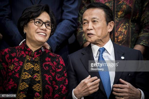 Sri Mulyani Indrawati Indonesia's finance minister left and Taro Aso Japan's finance minister speak before a group photograph at the spring meetings...