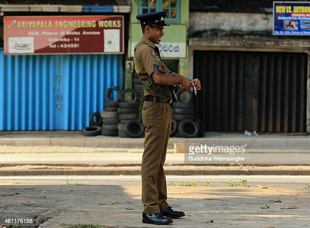 Sri police officer stands guard on the road during as ballot boxes are transported to counting centers on January 8 2015 in Colombo Sri Lanka The...