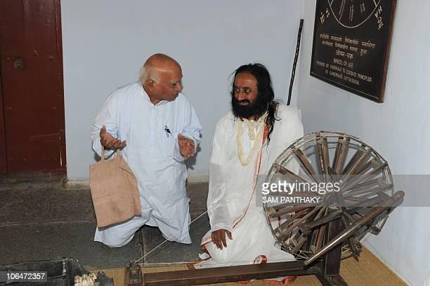 Sri Sri Ravi Shankar founder of the Art of Living Foundation talks with Amrut Modi Sabarmati Ashram Preservation and Memorial Trust Secretary during...
