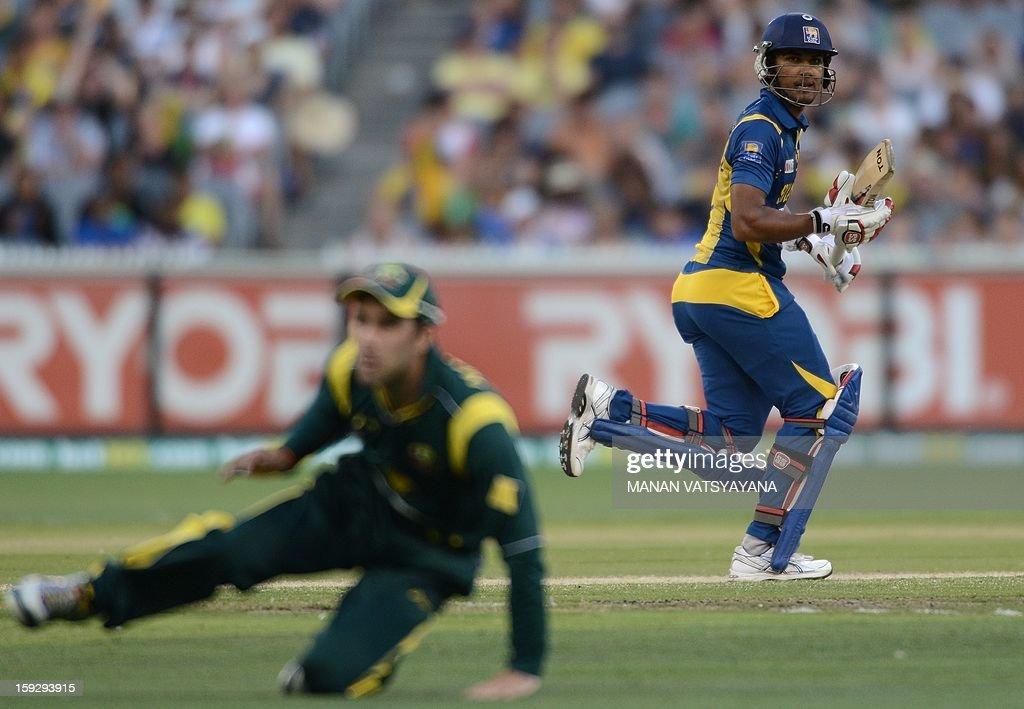 Srilankan batsman Dinesh Chandimal (R) takes a run past Glenn Maxwell (L) during the first one-day international between Australia and Sri Lanka at the Melbourne Cricket Ground on January 11, 2013. AFP PHOTO/ MANAN VATSYAYANA USE