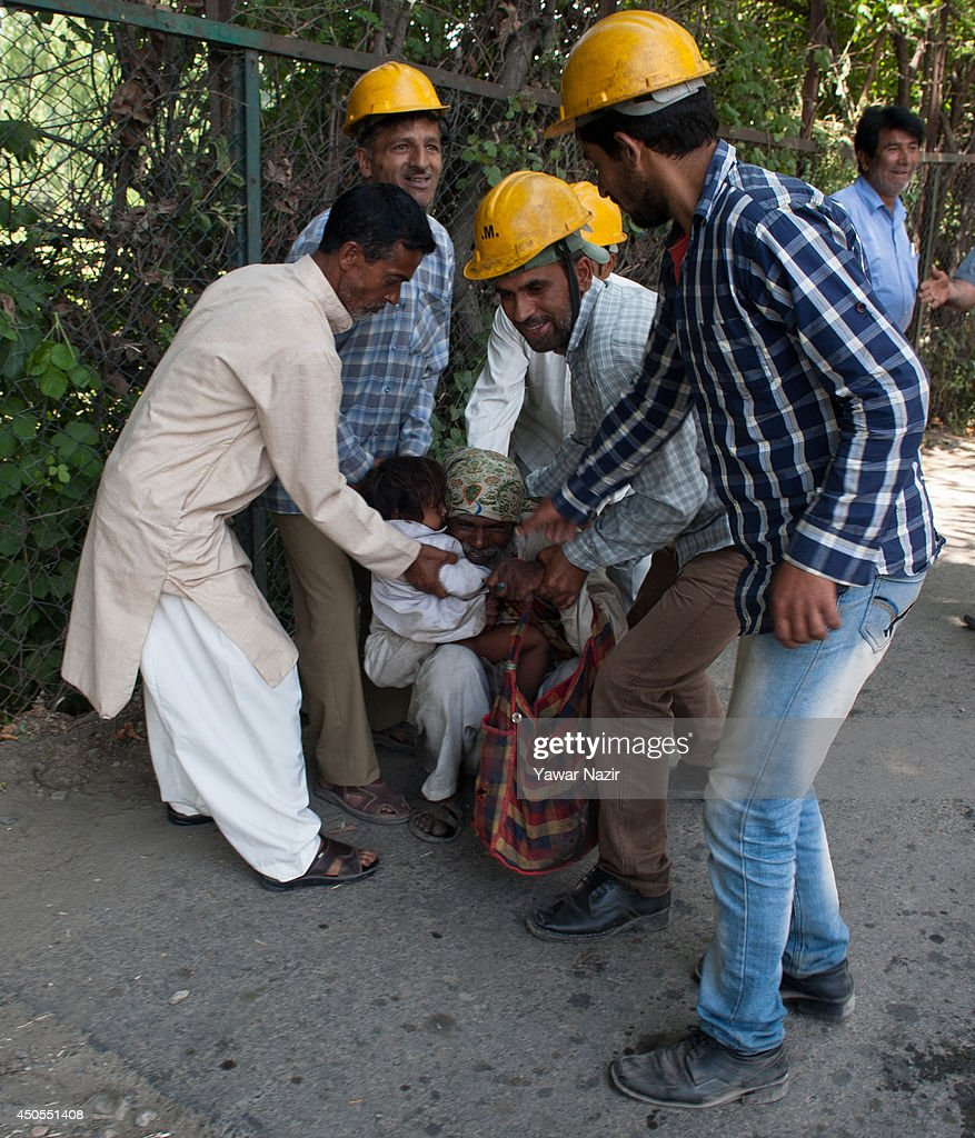 Srinagar Municipal Corporation workers detain an Indian beggar from a street on June 13, 2014 in Srinagar, the summer capital of Indian administered Kashmir, India. Dozens of governments civic body workers descended on the streets of Srinagar and detained scores of non local beggars who mostly arrive in the summer months from the Indian main land. Kashmir has witnessed an unprecedented influx of beggars from different parts of India during the last decade.