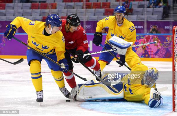 ss30 makes a save against Nino Niederreiter of Switzerland as Nicklas Backstrom defends during the Men's Ice Hockey Preliminary Round Group C game on...