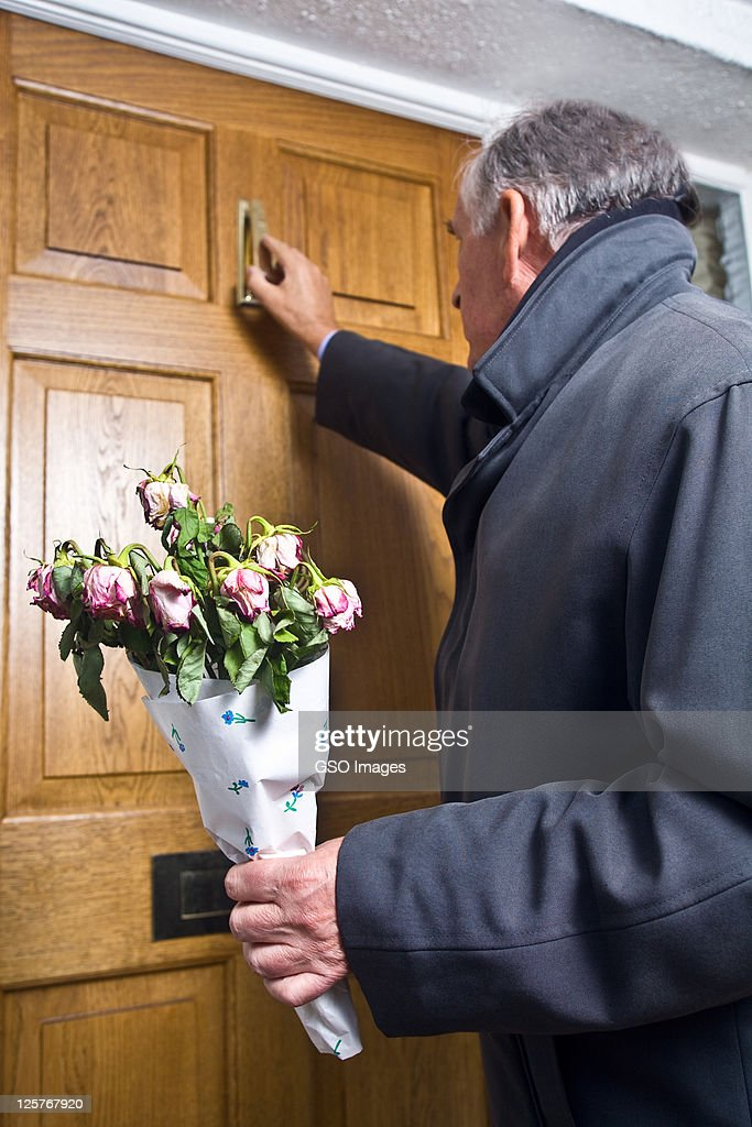 Ssenior man at door with withered bunch of roses