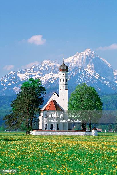 St. Coleman's Church in spring with snowcapped mountain in background, Schwangau, Germany